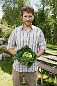 Young man holding savoy cabbage in market garden (outdoors)