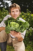 Man holding fresh savoy cabbage in garden