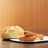 Frankfurters with mustard and bread roll