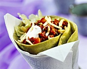 Tortilla filled with mince, cheese & sour cream in paper napkin