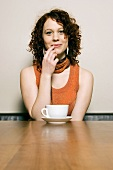 Young woman sitting at table with coffee cup