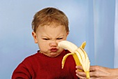 Woman offering banana to reluctant child