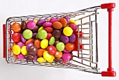 Multi-coloured candies in shopping cart, elevated view