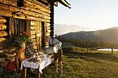 Bauer serviert Gästen Milch vor Almhütte