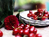 Cherries, peony and plates on table, close-up