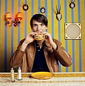 Young man eating hamburger