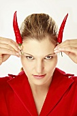 Young woman holding chili on head, simulating horns, portrait