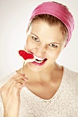 Young woman eating heart shaped lollipop, close-up, portrait