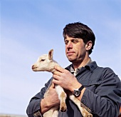 Mann mit jungem Lamm auf dem Arm