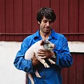 Bauer mit jungem Schwein auf dem Arm