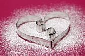 Heart-shaped biscuit cutter on icing sugar