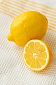 Whole lemon and half a lemon on tea towel
