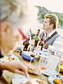 Seated man at an outdoor dinner party