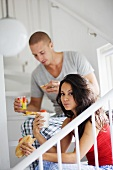Couple sitting on stairs eating breakfast