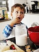 Little boy eating chocolate dough