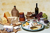 Cheese still life with bread, fruit, olives, nuts & red wine