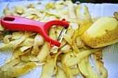 Potato peeler with potato peelings and potato