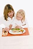 Mutter und Tochter sitzen am Tisch vor Gemüseterrine