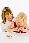 Girl drinking water with raspberry ice cubes