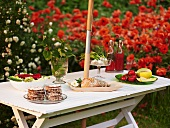 Salad, bread, vegetables & crackers on laid table in garden
