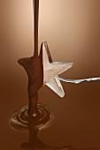Pouring melted chocolate over ice star