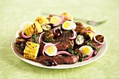 A beefsteak, corn, egg, olive and onion salad