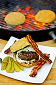 Barbecued hamburger with bacon and gherkin