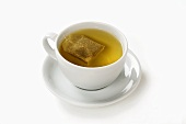 Peppermint tea with tea bag in cup and saucer