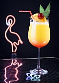 Cocktail in front of neon flamingo light