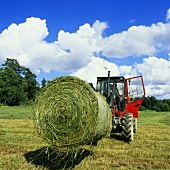 Tractor with a round bale of hay in a field