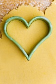 Heart-shaped cutter on biscuit dough