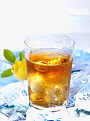 A glass of iced tea on ice with lemon