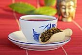 Rhubarb root in wooden scoop with tea
