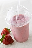 A strawberry shake in plastic take-away cup with fresh strawberries