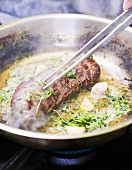 Frying pork fillet with cress and garlic in frying pan