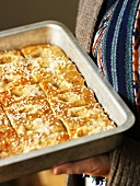 Woman serving sweet bread buns in baking tin