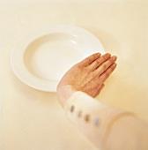 Frau schiebt den leeren Teller weg