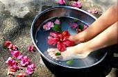 Frauenfüße in einem Fußbad mit Blüten