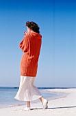 Woman wearing orange turtleneck sweater and airy skirt walking on beach