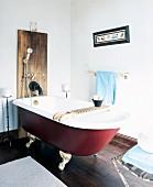 Freistehende Vintage Badewanne mit Ablage vor Holzpaneel an Wand mit Duscharmatur in schlichtem Badezimmer