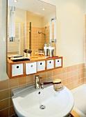 Bad, Waschbecken, Wandspiegel, darunter kleine Schubladen