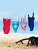 Different coloured swimwear hanging on string at the beach.