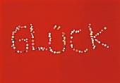 Glück - geschrieben aus verschiedenen Pillen, Symbol