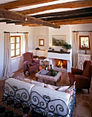 Living room with beamed ceiling, rustic furniture and fireplace