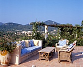 Terrace with brick bench and wicker furniture in Mallorca, Spain