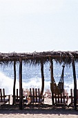 Chairs and hammock under shack on beach in Acapulco