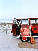 Red bus with open doors parked on beach