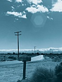 View of country road and electricity pylon on American desert landscape, USA, toned image