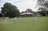Crickers in winter sportswear playing cricket on green ground, England, UK