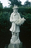 White statue of a medieval English gardener in the garden